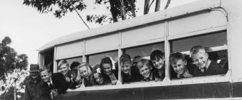 Black and white photo, kids on a school bus