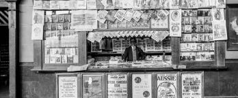 Black and white image of man working at newspaper stand, Spencer St train station