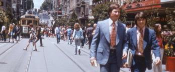 People in the 1970s walking along Bourke Street. Two men in suits are in the foreground.