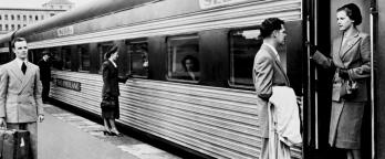 Old black and white image of man farewelling woman at train