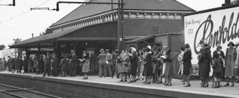 Black and white photo of people waiting on a railway station platform