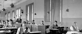 Black and white photo of people sitting at desks