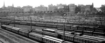 Black and white photo of trains in city rail yard