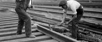 Black and white photo of men working on railway tracks