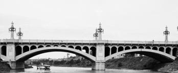 Black and white photo of bridge over a river