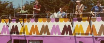 colourful photo of a band playing on top of a Big M branded pink bus