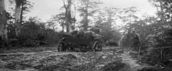black and white image of men with horse and cart walking through muddy track in the bush