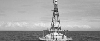 black and white photo of a buoy on the ocean