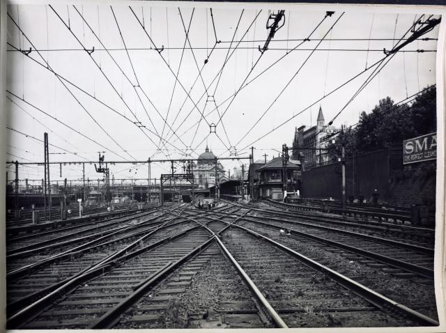 black and white photo of tracks in the foreground and flinders street station in the back