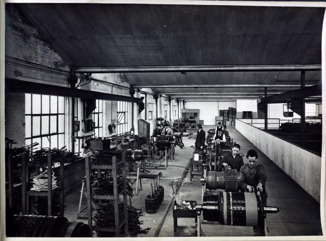 black and white image of men working in a workshop with machinery