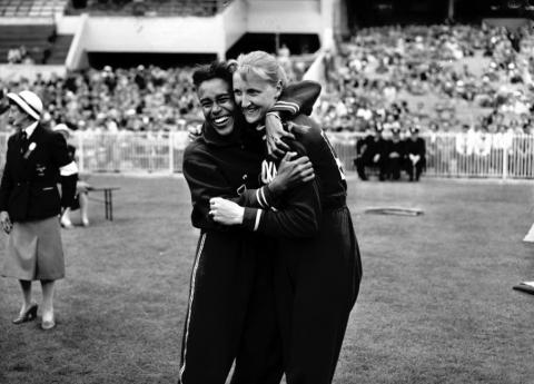 black ans white image of 1956 women long jump olympians embracing.