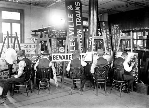 black and white image of sign writers at work.