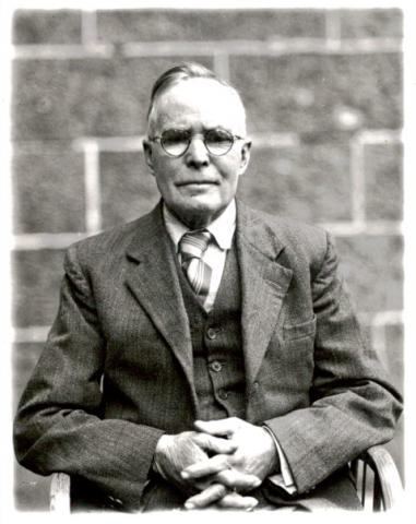 black and white photo of old man wearing glasses, facing the camera